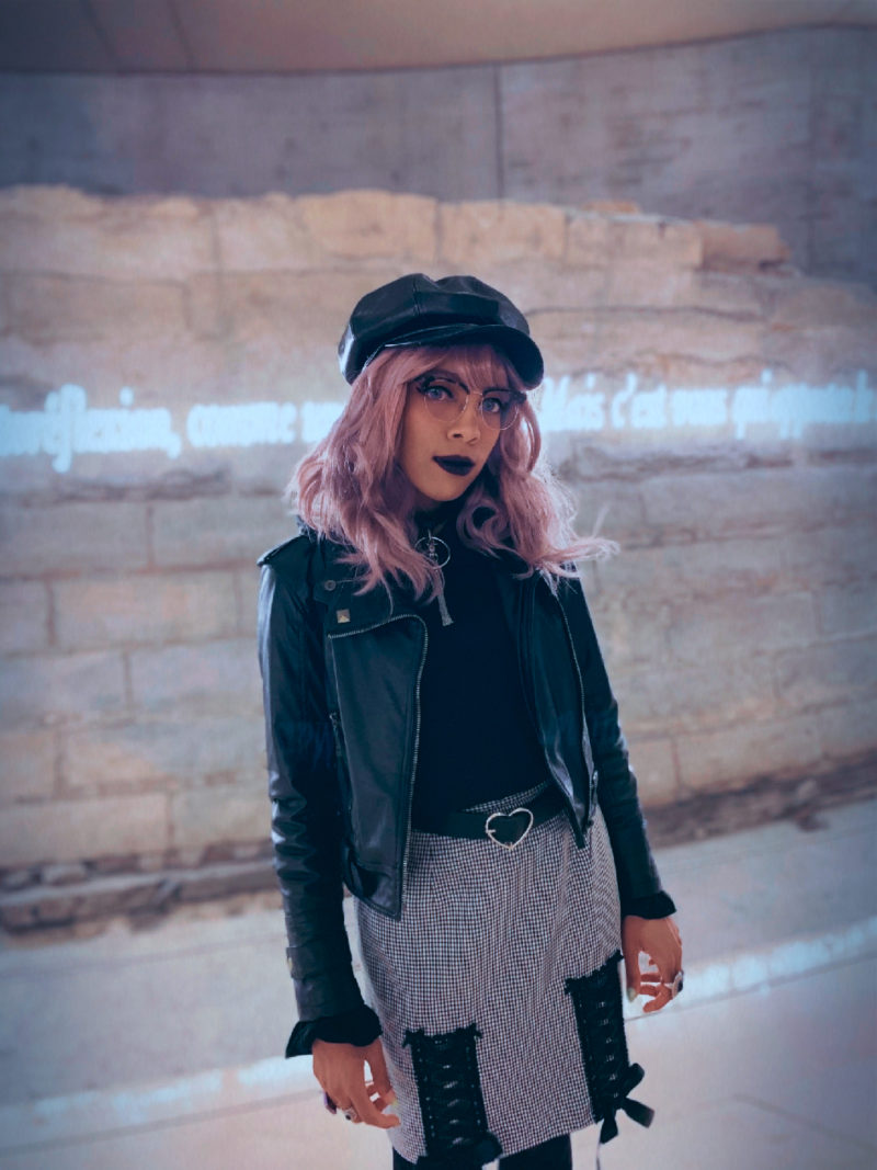 Aria Todd wearing a black cap, leather jacket, and plaid pencil skirt in front of neon lettering