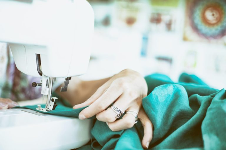 The hand of someone sewing a green plush material on a sewing machine