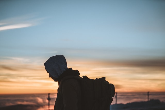 Figure in shadow of a person in a hoodie with a large backpack in front of a dusk sky