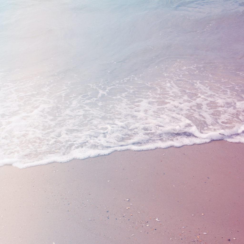White foam of the ocean on a pastel sandy beach